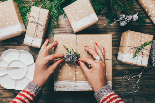 woman wrapping christmas presents in a crafty way - christmas green stock photos and pictures