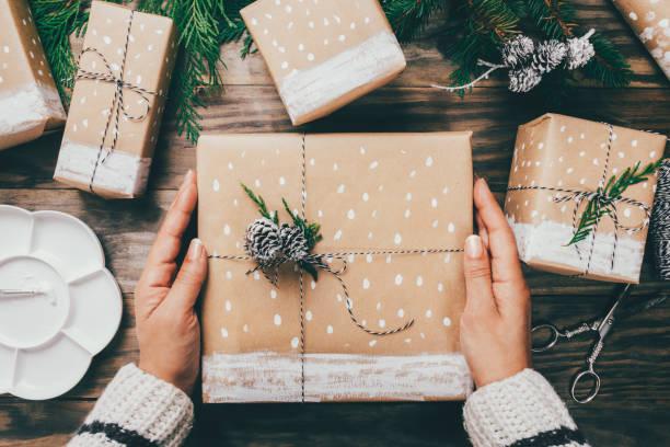 frau verpackung weihnachten präsentiert auf listige weise - eco bastelarbeiten stock-fotos und bilder