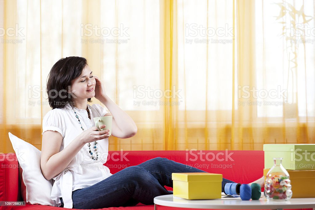Woman Wrapping Gifts and Relaxing on Couch royalty-free stock photo