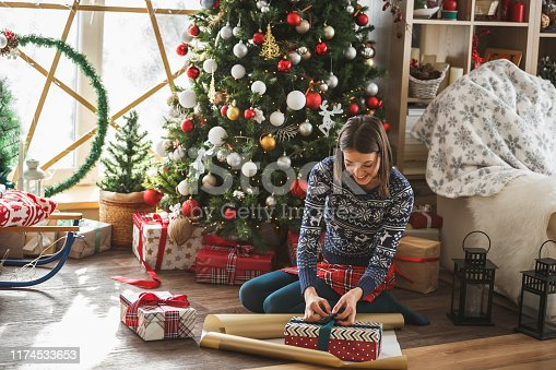 Happy young woman is wrapping and decorating gifts under the Christmas tree in her apartment.