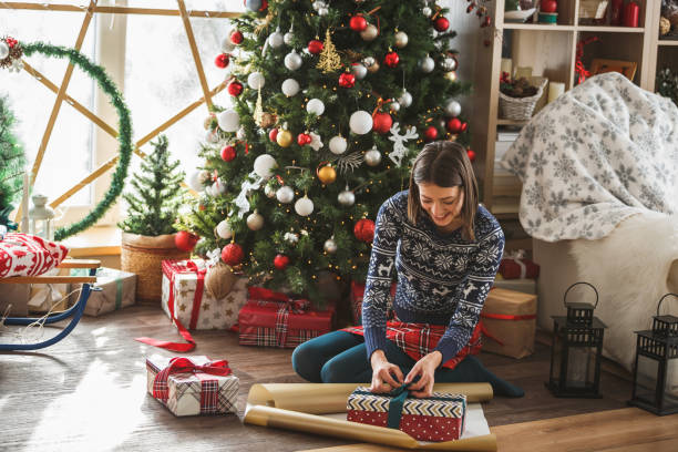Woman wrapping gifts by the Christmas tree stock photo