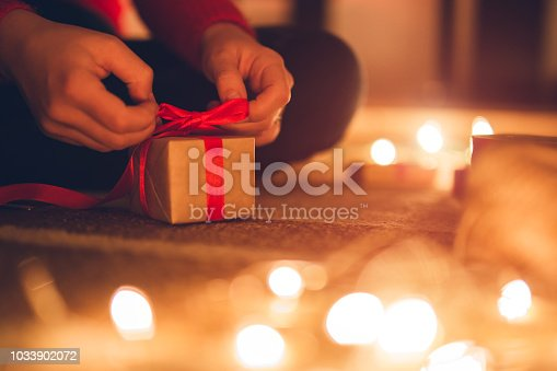 Young woman wrapping gift boxes, surrounded with fairy lights
