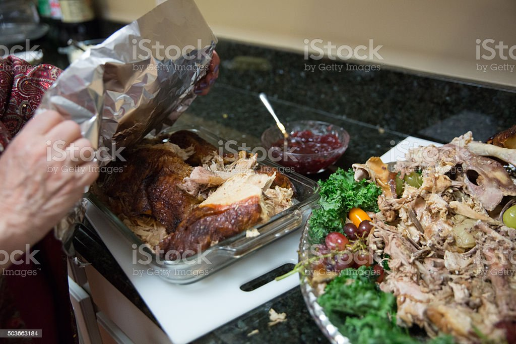 Woman wraps up leftover turkey from Thanksgiving dinner stock photo