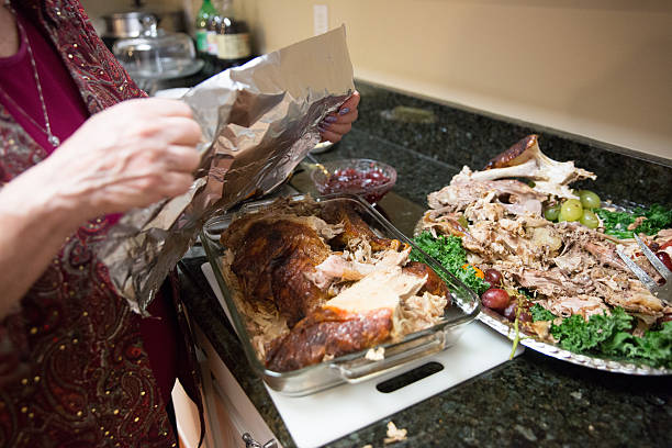 Woman wraps up leftover turkey from Thanksgiving dinner Caucasian woman whose face isn't visible is covering a glass pan of turkey leftovers with tin foil. The platter the turkey was on is beside it with the carcass and bits of turkey on it. They are sitting on a granite kitchen counter. Taken with a Canon 5D Mark 3. leftovers stock pictures, royalty-free photos & images