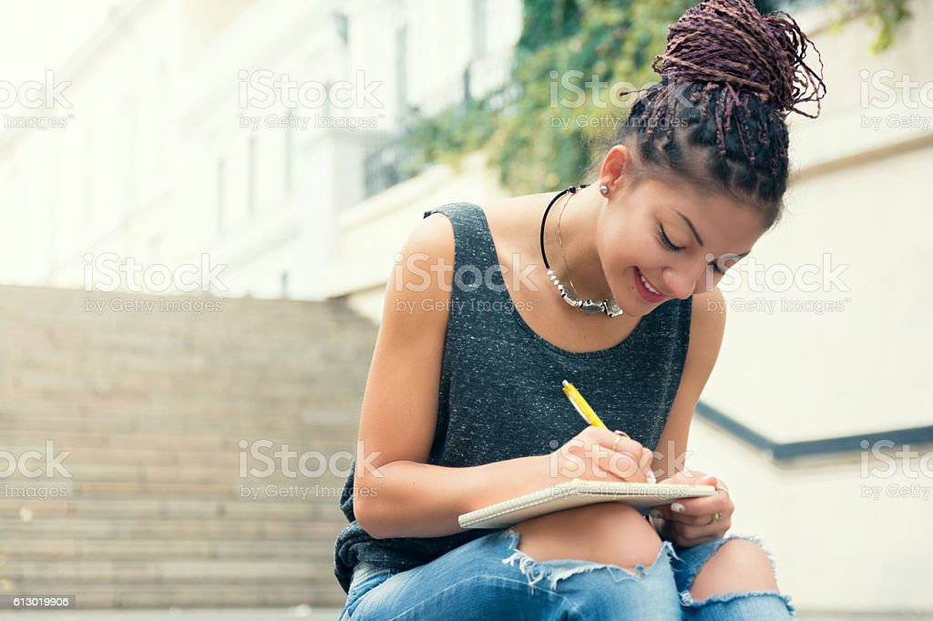 Woman write down the notes at the street, smiling stock photo