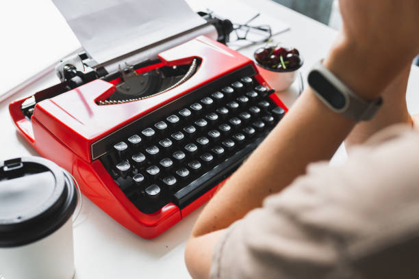Woman writer thoughtfully working on a book on her Desk red typewriter stock photo