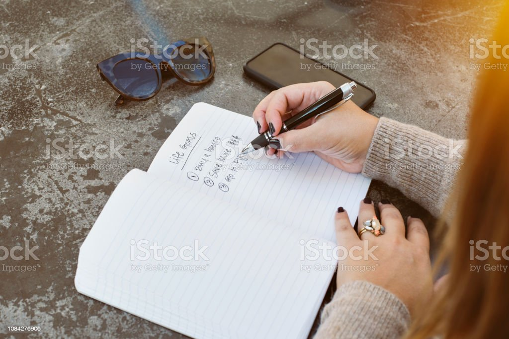 Young female writes her life goals with a pen and paper. Sunglasses...
