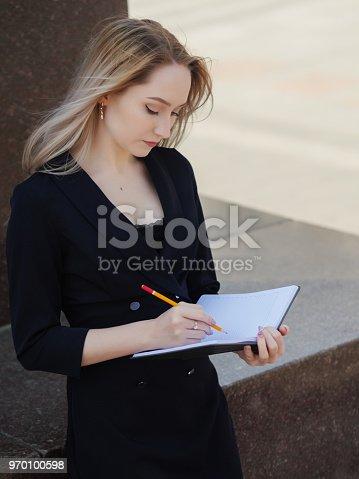1147767708 istock photo Woman writing at notebook. 970100598