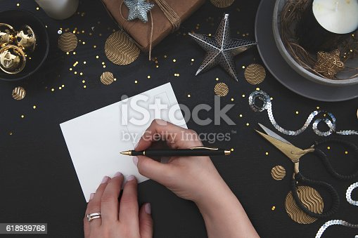 istock Woman writing blank card with Christmas deco on dark wood 618939768