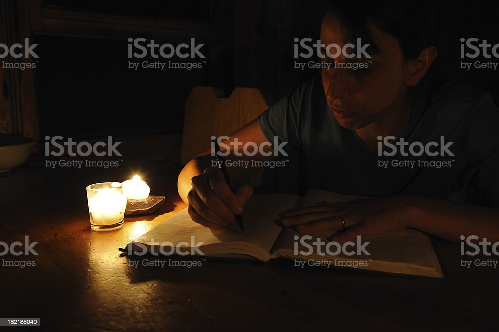 Woman Writing by Candlelight stock photo