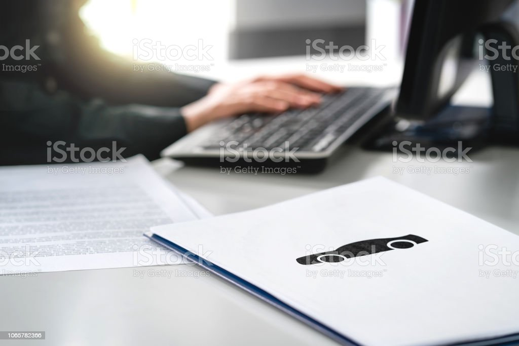 Woman writing car insurance document, bank loan application or lease contract. Car dealer working with computer in dealership. Buying or selling new or used vehicle online. stock photo
