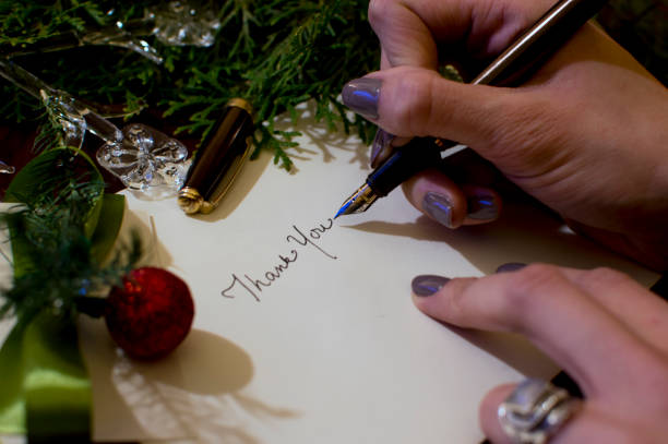 Woman writing Christmas card writing thank you with evergreen  and ornaments background stock photo