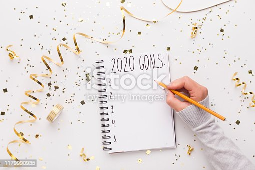 2020 concept. Woman writing down in notepad with 2020 goals, copy space, Christmas background