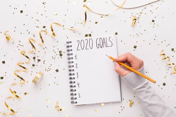 mujer escribiendo en el bloc de notas con metas de 2020 - determinación fotografías e imágenes de stock