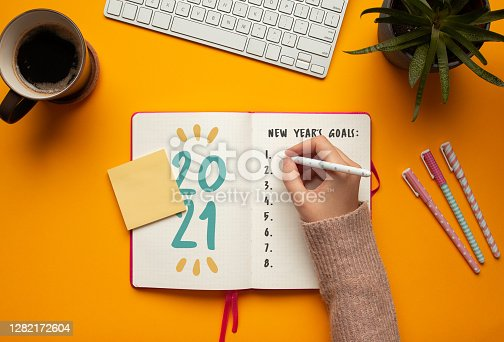 Stock photo of woman writing goals in a 2021 new year notebook on yellow background