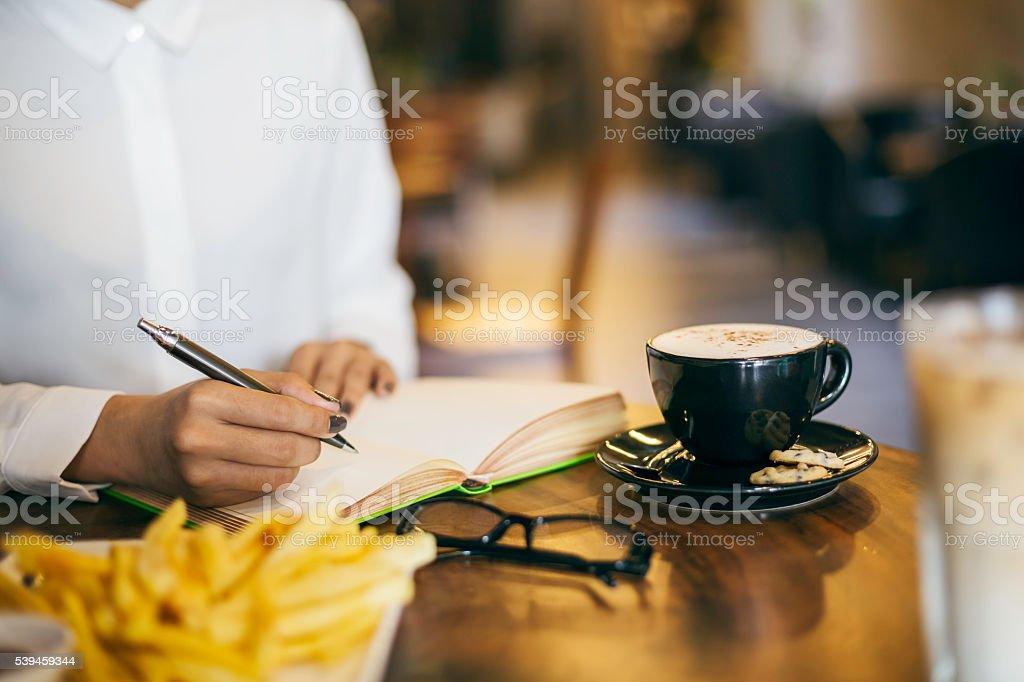 Frau schreiben Ihrem notizbuch – Foto
