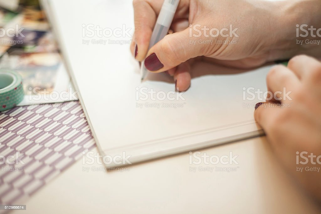 Woman writing in a baby book stock photo