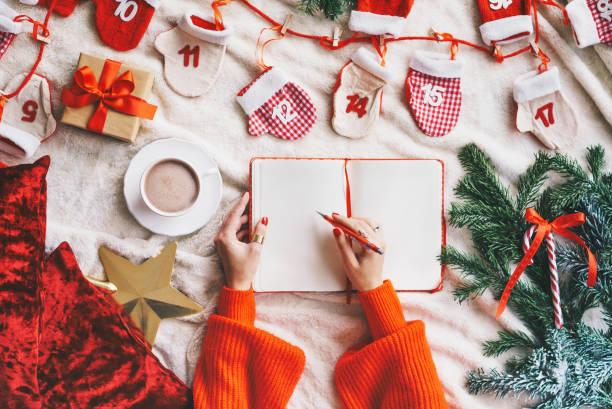 Frau schreibt in einem leeren Notizbuch - Weihnachtskonzept flach liegen – Foto
