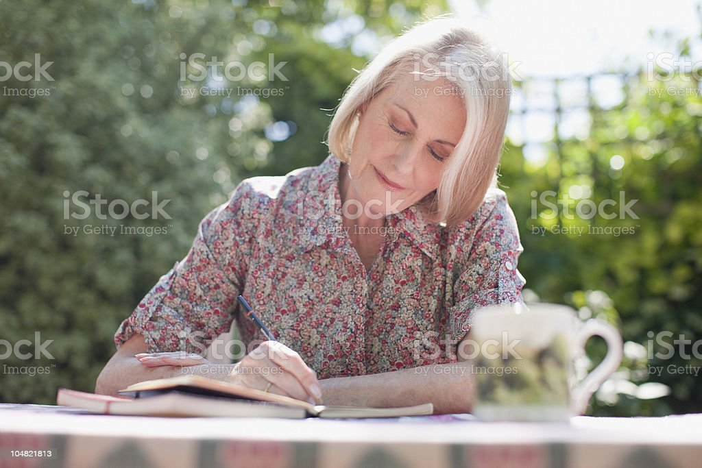 Woman writing in journal at patio table stock photo