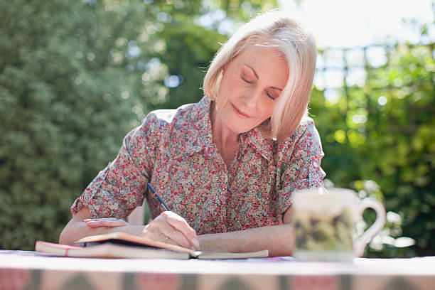 Woman writing in journal at patio table  diary stock pictures, royalty-free photos & images