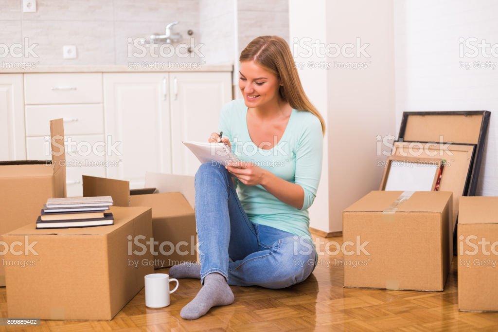 Frau schreiben in Notebook im neuen Zuhause – Foto