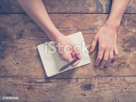 istock Woman writing in notepad at wooden table 479294046
