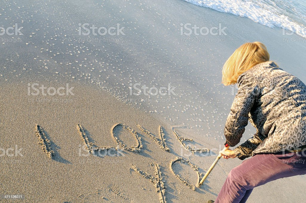 Woman Writing in the Sand on Valentine's Day stock photo