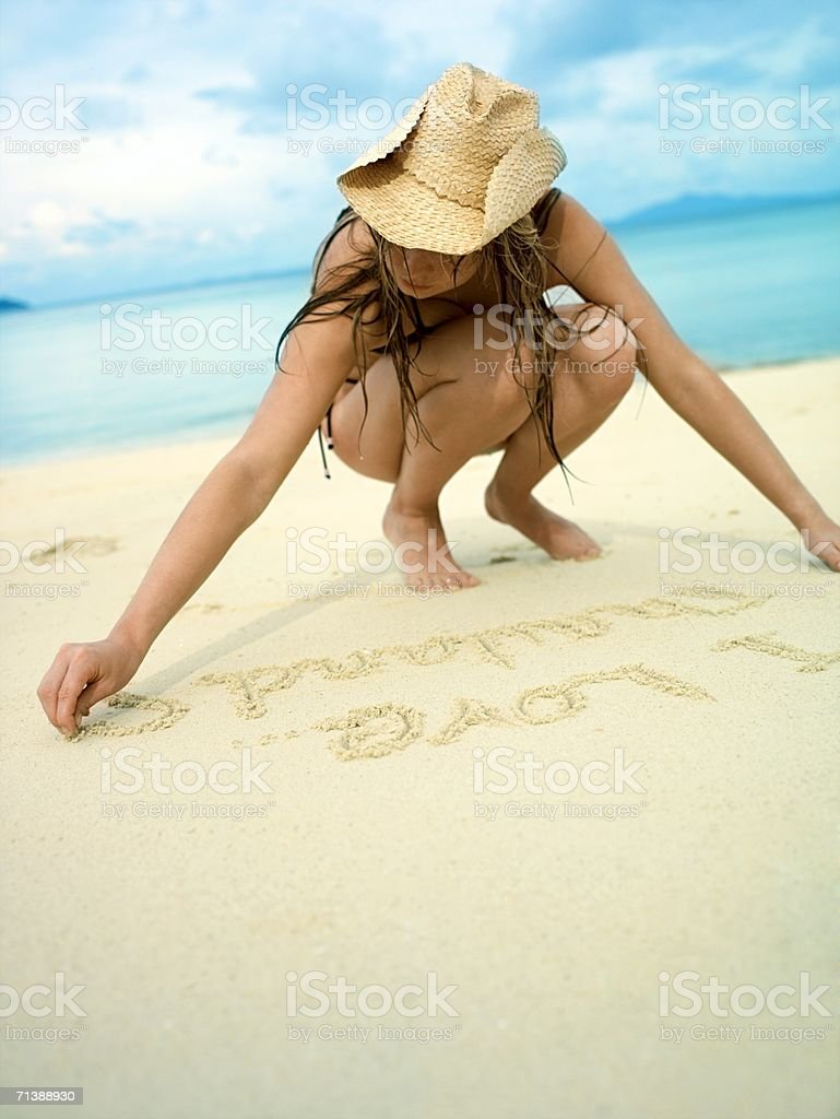 Woman writing in the sand royalty-free stock photo