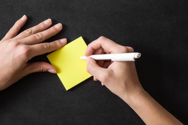 frau in der gelben klebezettel zu schreiben. arbeiten auf dem tisch. leeren platz für wichtige ideen, pläne, erinnerungen, nachrichten, komplimente oder anderen text mit positiver stimmung. erinnerung-konzept. - unterrichtsplanung vorlagen stock-fotos und bilder
