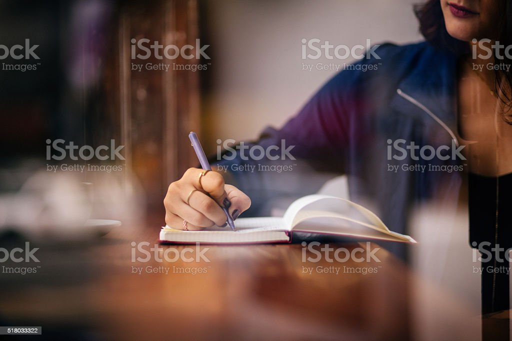 Woman Writing Journal at Window Seat in Coffee Shop stock photo