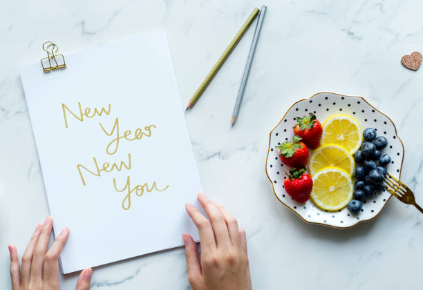 Woman writing New Year New You stock photo