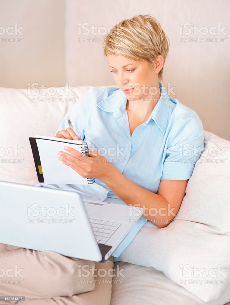 Woman writing notes from the internet royalty-free stock photo
