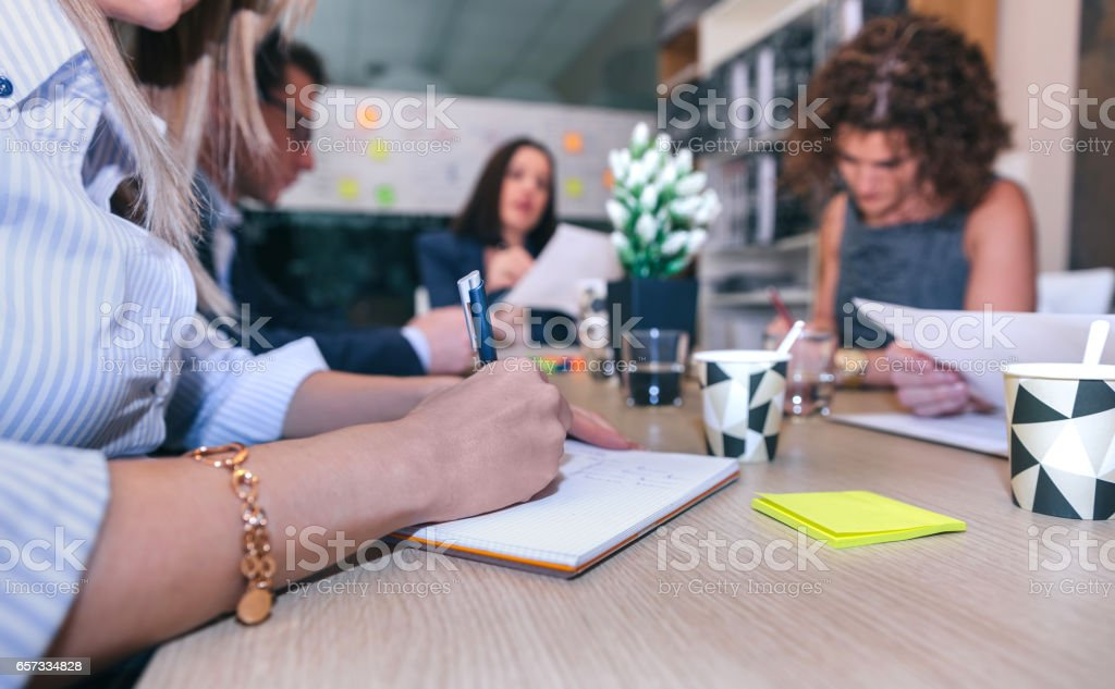 Woman writing notes in a meeting with teamwork stock photo
