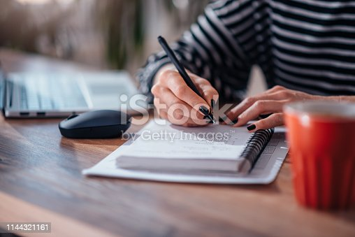 Woman writing notes in notebook in the office