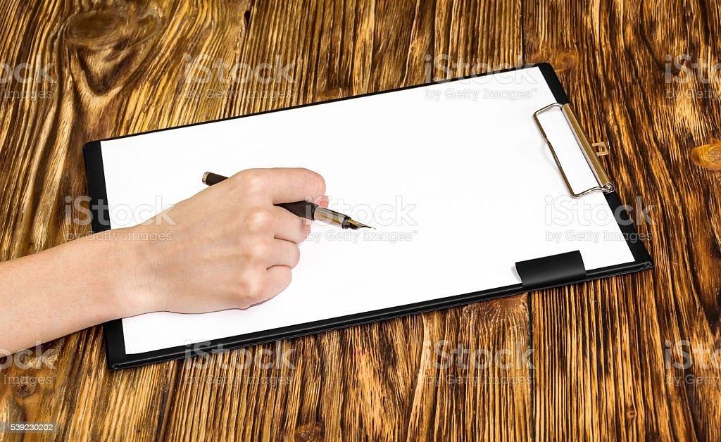 Mujer escribiendo en un portapapeles sobre una hoja en blanco foto de stock libre de derechos