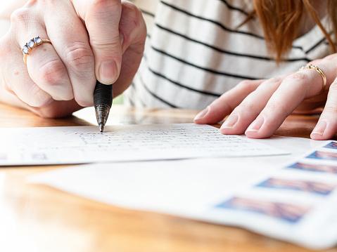 Woman Writing on a Postcard