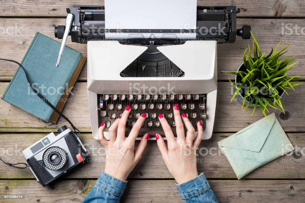 Woman writing on an old typewriter stock photo