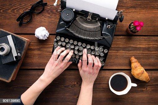 istock Woman writing on an old typewriter 926139890