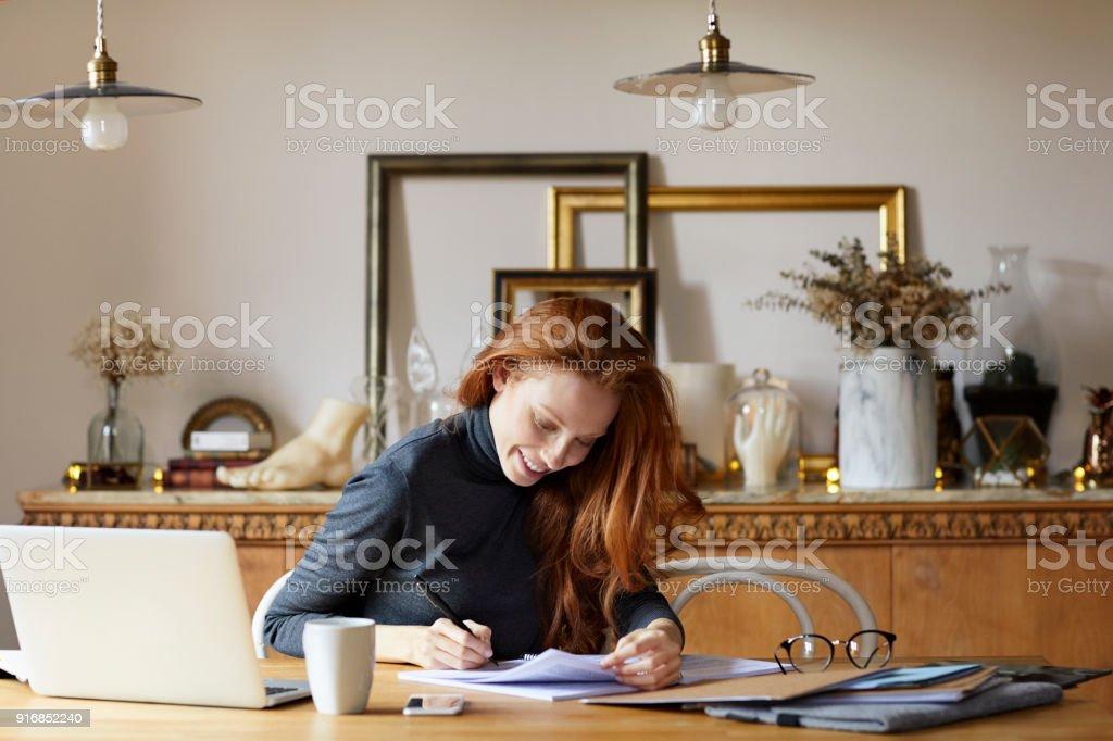 Frau auf Dokumente in Tabelle schreiben – Foto