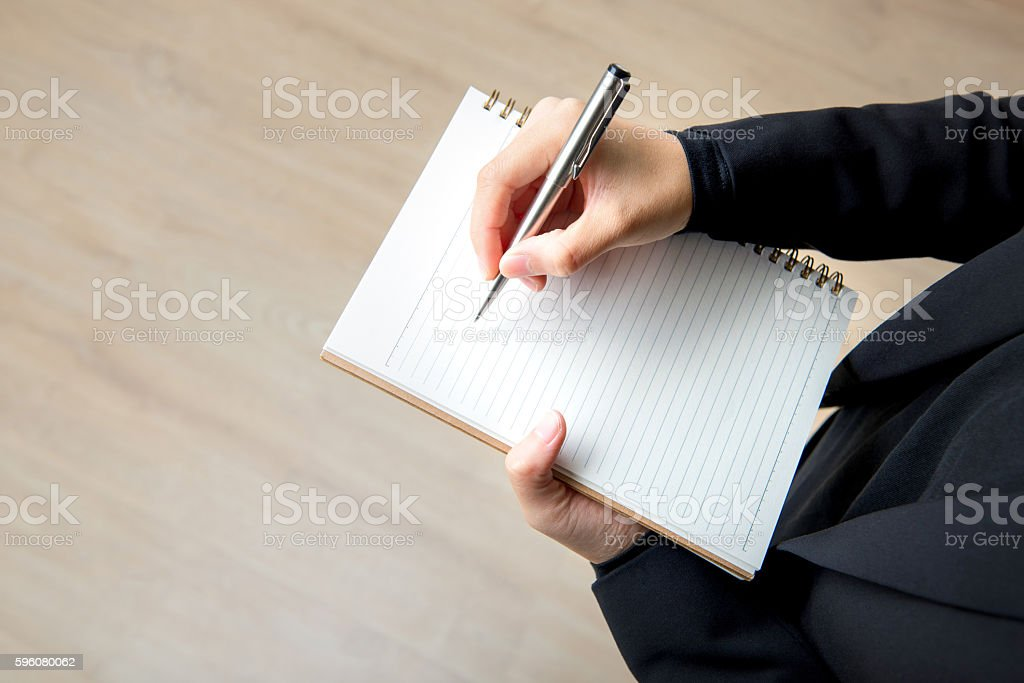 Woman writing on empty notebook with pen royalty-free stock photo