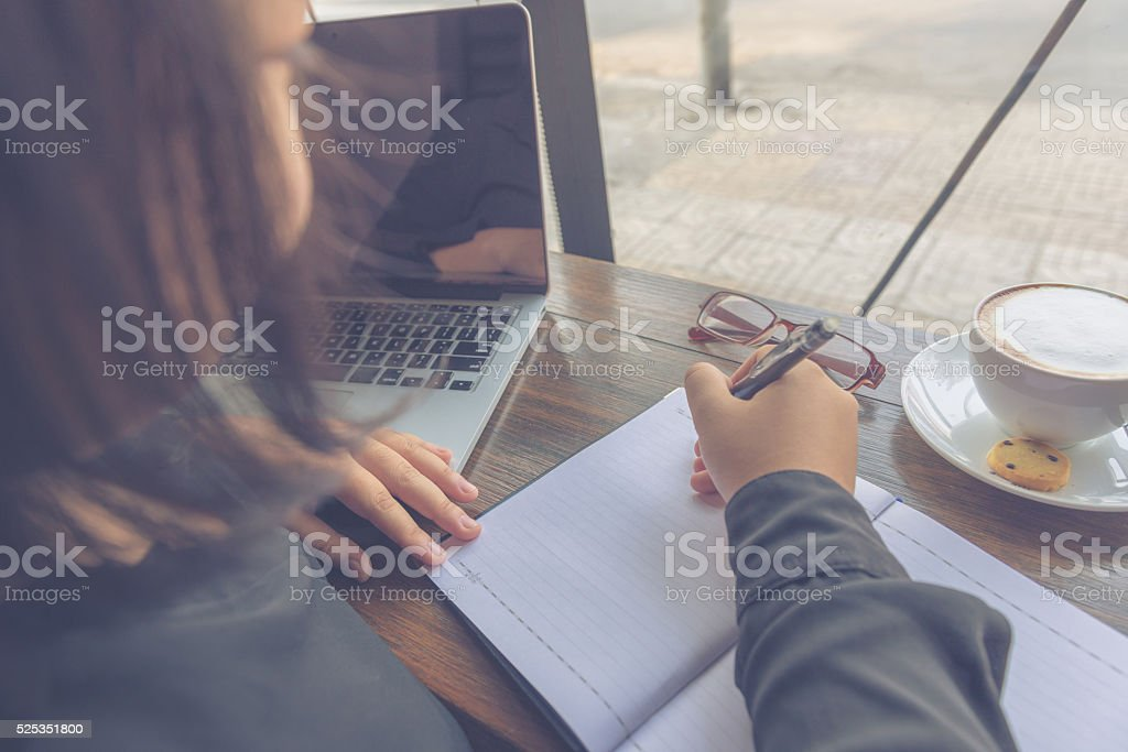 Woman writing on notebook beside laptop and glasses stock photo