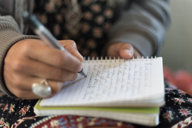 Woman writing on notepad stock photo