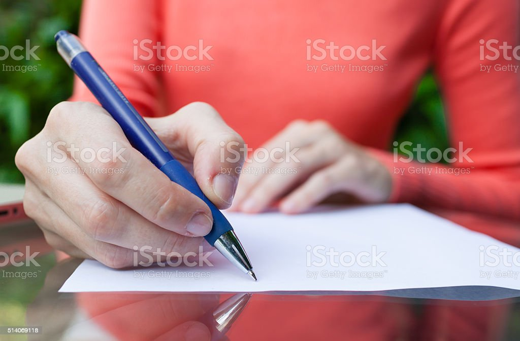 Woman writing on paper stock photo