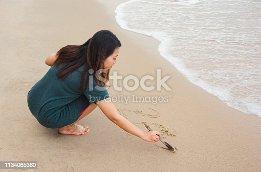 Woman writing on sandy beach with tree branch