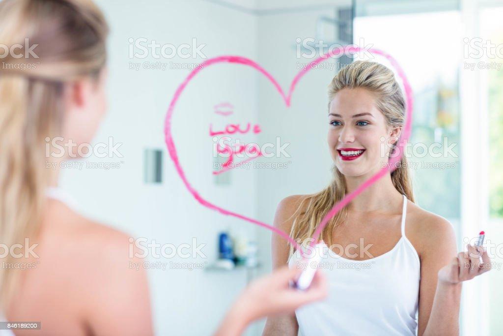 Mujer en el espejo con lápiz labial - foto de stock
