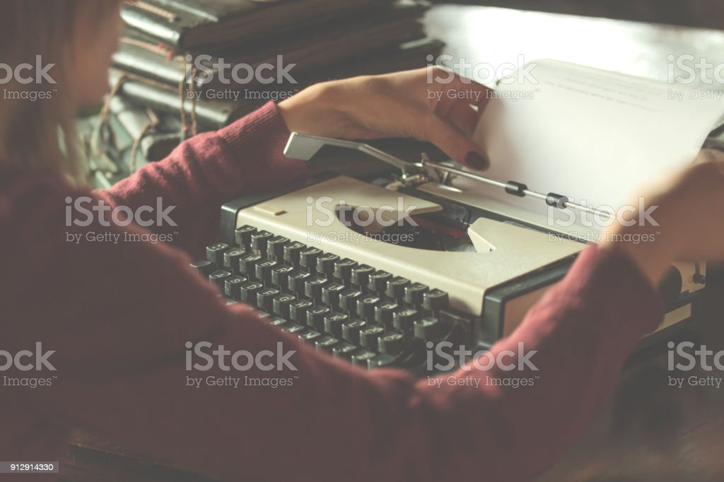 Woman writing on the vintage typing-machine. Shallow depth of field on keyboards. stock photo