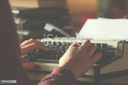 istock Woman writing on the vintage typing-machine. Shallow depth of field on keyboards. 914432368