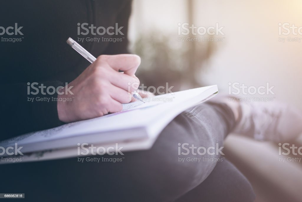 woman writing or scribbling on a notepad that is resting on her legs – Foto