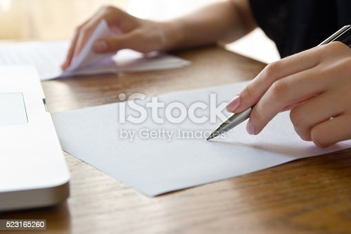 woman working with text using paper and laptop