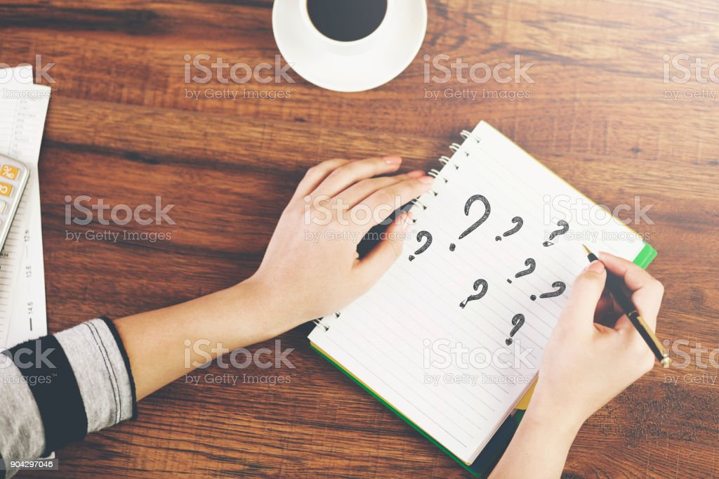 woman writing question mark stock photo